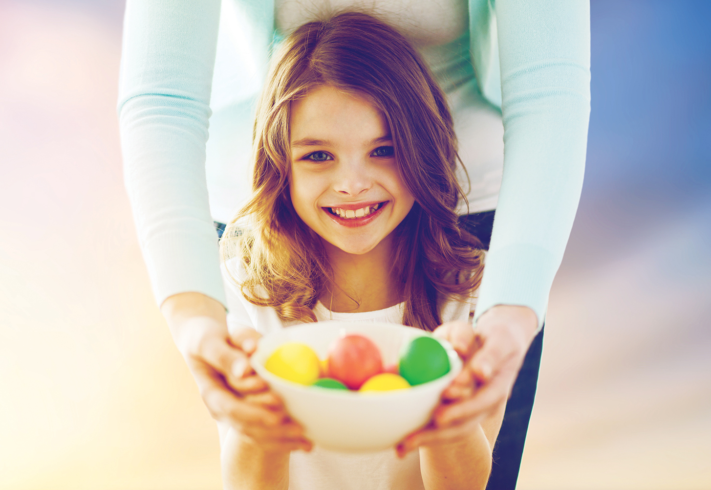 easter, family and holiday tradition concept - close up of little girl and mother holding colored eggs over sky background