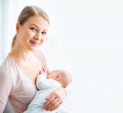 beautiful young mother breastfeeding baby and smiling at camera