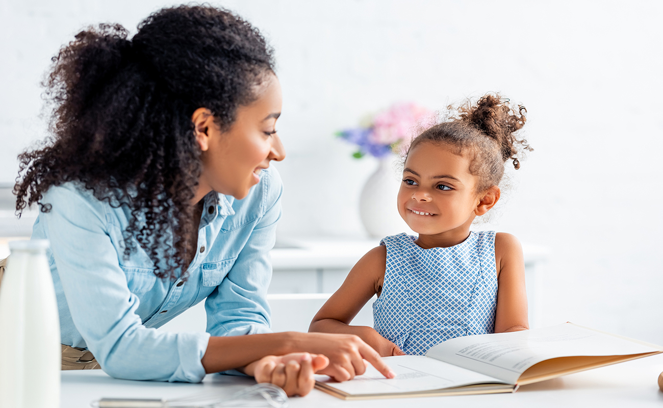 smiling african american mother and daughter looking at each other and choosing recipe from cookbook in kitchen