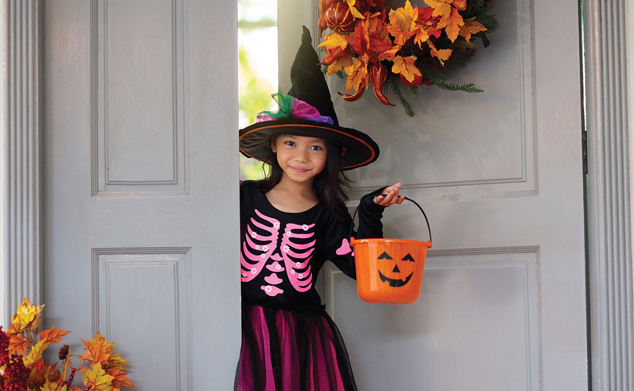 Asian child in witch costume and hat on Halloween. Kids trick or treat, play with pumpkin and spider in autumn park. Little Chinese girl in skeleton dress. Family fun in fall.
