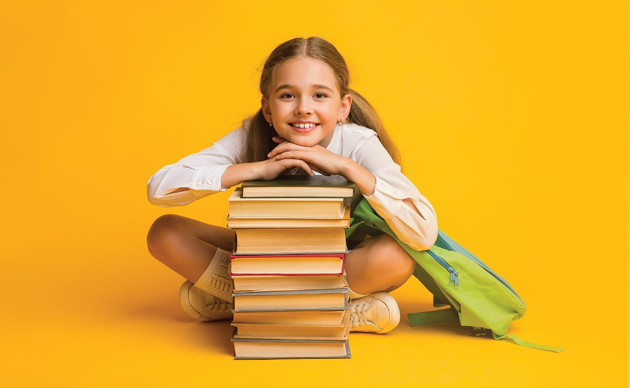 Back To School Concept. Cute Little Schoolgirl Smiling To Camera Sitting With Backpack At Stack Of Books Over Yellow Background